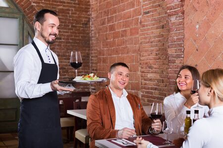 Friendly smiling male waiter bringing order to visitors in country restaurant