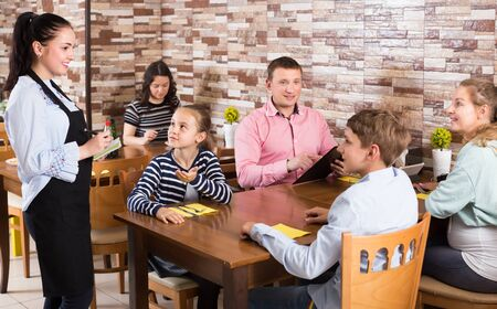 Positive hospitable waitress helping visitors with menu taking order in cafe