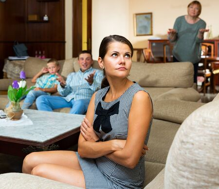 Portrait of young woman upset after discord with husband and mother at home 写真素材