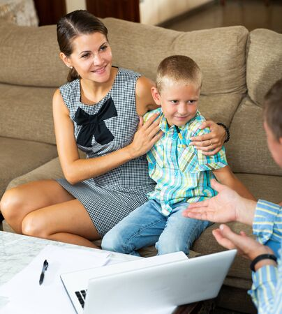 Professional consultant making presentation with laptop for woman with little son at home