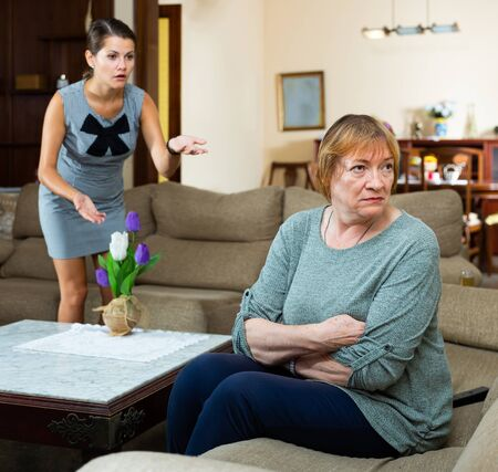 Elderly mother and adult daughter scandal in domestic interior