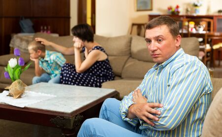 Unhappy man sitting  at sofa after family quarrelling, woman with son  on background 写真素材 - 129663059
