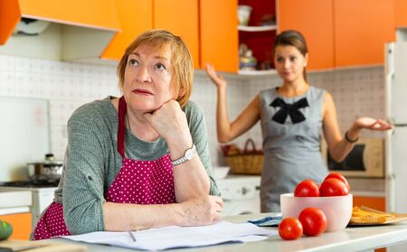 Portrait of upset elderly mother sitting in cozy home kitchen while dissatisfied adult daughter moralizing her Stok Fotoğraf