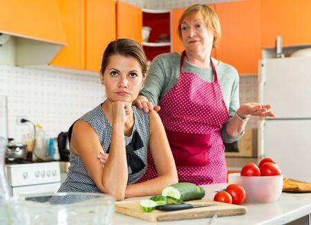Portrait of upset young woman with worried elderly mother reprimanding her sitting in cozy home kitchen