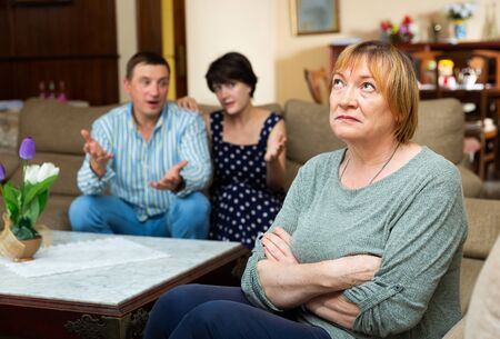 Portrait of upset offended elderly woman sitting on sofa at home on background with couple berating her