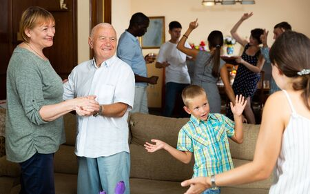 Cheerful elderly couple dancing during family holiday celebration together with their children and grandkids at home Stock Photo - 129663009