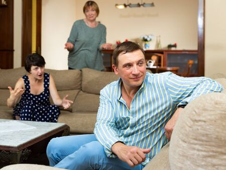 Upset husband apart from her wife and senior mother quarrelling 写真素材 - 129662978