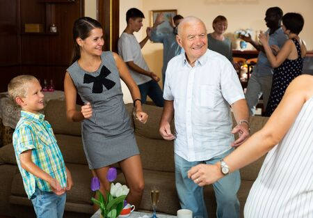 Adults and children dancing at a party at home