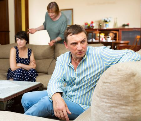Upset husband apart from her wife and senior mother quarrelling 写真素材