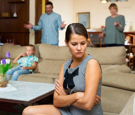 Upset young woman sitting  at sofa during quarrelling between family on background at home 写真素材 - 129662989