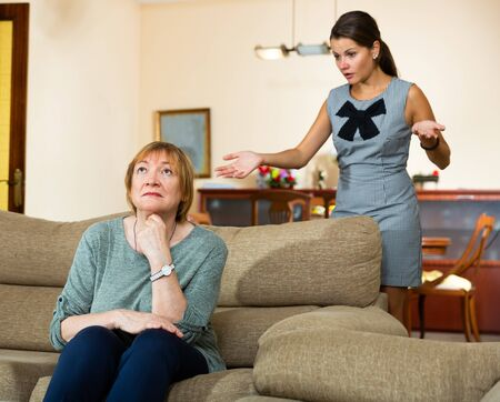Upset elderly woman sitting on sofa at home on background with daughter berating her