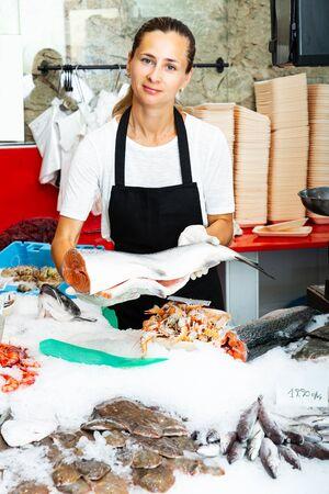 Jeune poissonnière positive offrant du saumon frais réfrigéré à vendre dans un magasin de fruits de mer