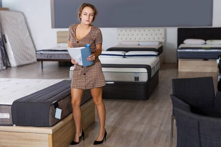 positive young woman reading brochure while choosing new mattress in store Stock Photo