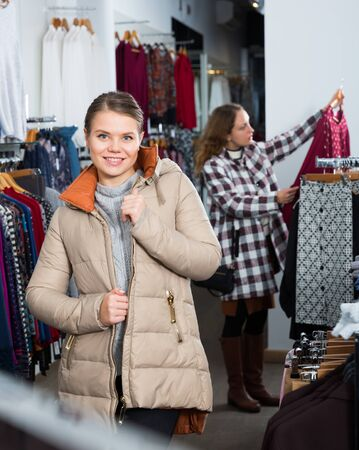 Young positive woman standing in overcoat in outerwear clothing boutique