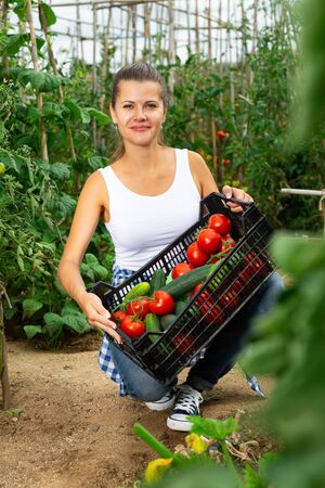Girl farmer with a box of vegetables in the garden