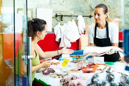 Vendeuse positive et confiante debout derrière le comptoir du magasin de fruits de mer, démontrant du saumon cru frais à une acheteuse Banque d'images