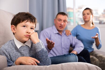 Portrait of offended boy after quarrel with parents sitting on sofa at home