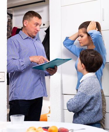 Portrait of frustrated woman and her preteen son talking to debt collector visiting them at home and demanding to pay debts Banque d'images