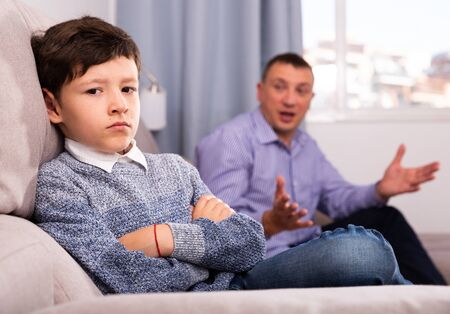 Frowning tweenager listening to reprimanding from his father at home