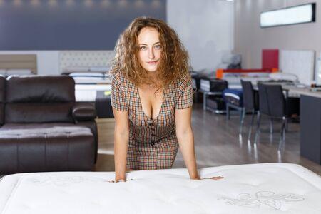 Joven mujer positiva eligiendo el colchón correcto en la tienda de muebles para el hogar