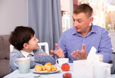 Portrait of upset father and  offended son arguing in domestic interior