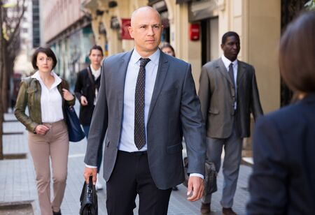 Focused business man with briefcase in hand walking on city street in crowd of people Foto de archivo - 129949693