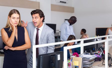 Angry boss blaming young woman office worker in office