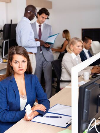 Portrait of frustrated unhappy young business woman in coworking space with busy colleagues behind 写真素材 - 129697280
