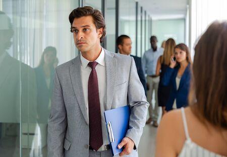 Fokussierter Mann im Anzug, der unter Büroangestellten durch das Büro geht