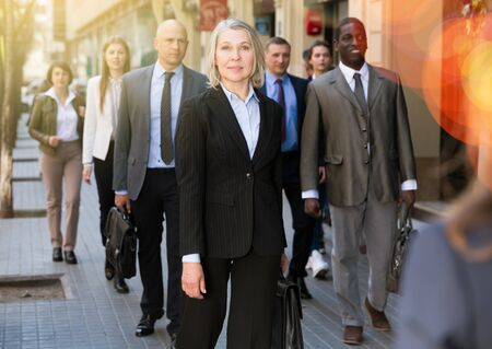 Elegant mature business woman walking on modern city street at rush hour Stock Photo