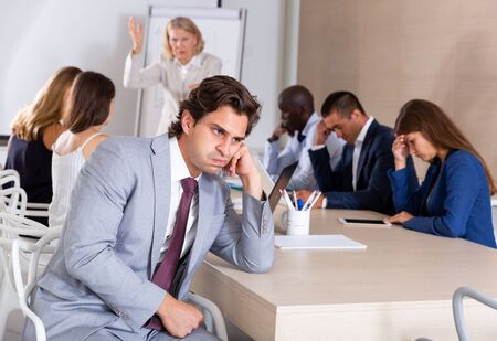 Upset and tired businessman sitting at desk in office on background with angry female boss scolding subordinates