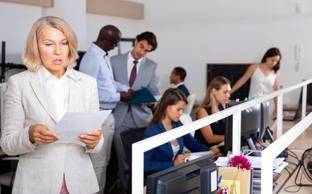 Puzzled upset   and confused mature businesswoman standing with papers in hands in coworking space, thinking about problem to solve