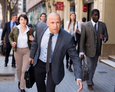 Adult man in business suit hurry up and walking fast down the street among people