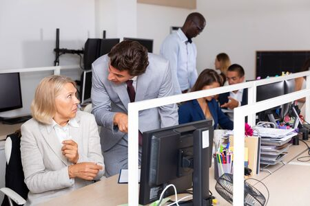 Angry boss blaming adult female office worker in office Stock Photo