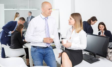 Smiling business colleagues enjoying free time and conversation, relaxing at coffee break