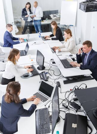 Top view of business people working and communicating together in modern open plan office
