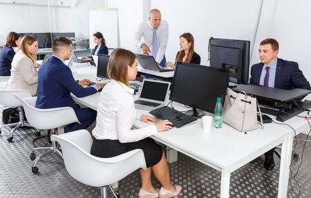 Group of smiling  positive successful business people during daily work in modern co-working space