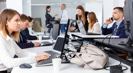 Young cheerful positive businesswoman concentrated on work with laptop in coworking space
