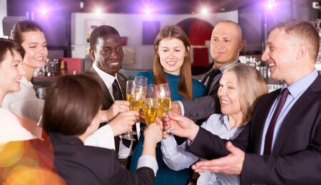 Cheerful males and females clinking glasses on corporate party