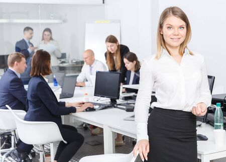 Portrait of happy young business woman is standing  in coworking space with working colleagues behind