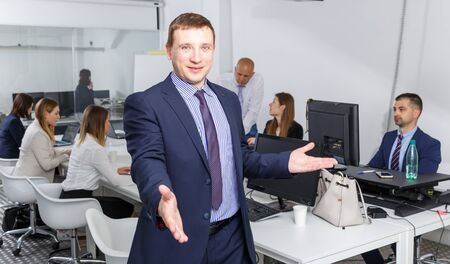 Successful businessman standing in office with open hand ready for handshake