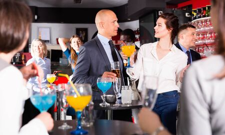 Glad positive smiling male and female colleagues having fun on corporate party in bar