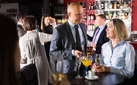 Pleasant mature woman having nice time with male colleague on corporate party in nightclub
