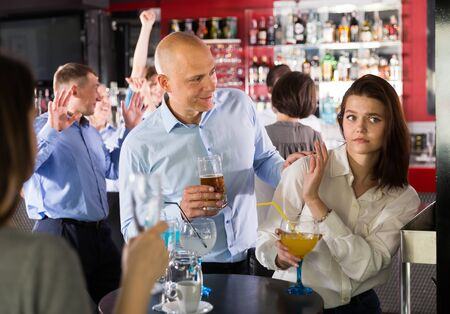 Tipsy man trying to seduce young female colleague on office party at nightclub Archivio Fotografico - 129800881