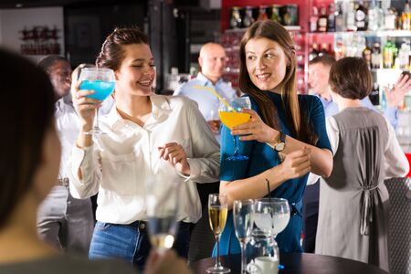 Portrait of two young women drinking cocktails and talking on corporate party