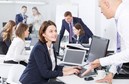Attractive smiling girl talking to male colleague in coworking space