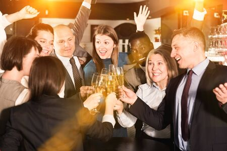 Happy colleagues clinking a glasses of champagne on corporate party Stock Photo
