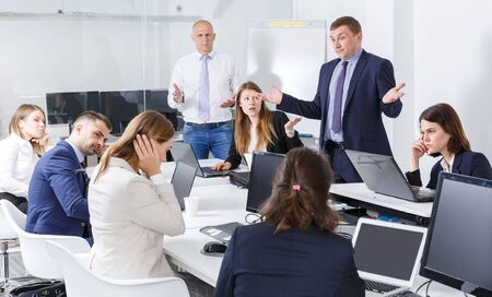 Active manager expressing dissatisfaction with teamwork of colleagues at meeting 写真素材