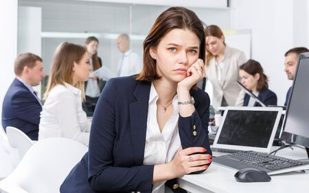 Portrait of upset young woman foreground in coworking space