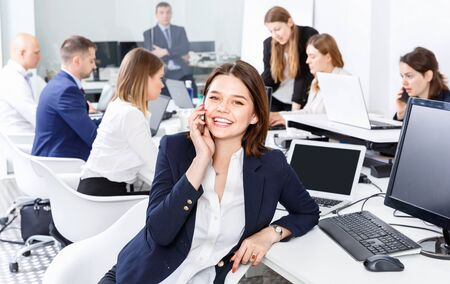 Successful young happy cheerful positive smiling business woman with phone relaxing at workplace in modern office